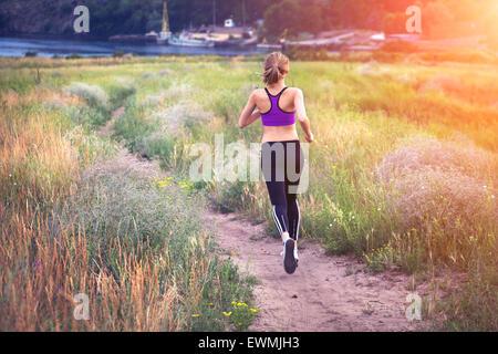 Jeune femme tournant sur un chemin rural au coucher du soleil en été. Fond sports Lifestyle Banque D'Images