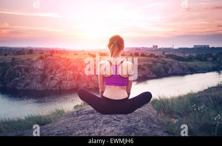 Young woman practicing yoga on the hill au coucher du soleil près de la rivière. Banque D'Images