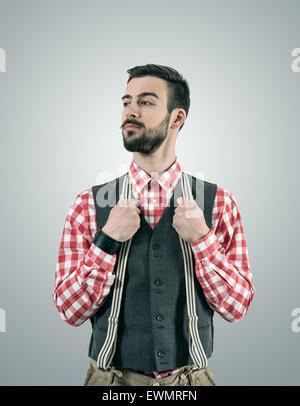Portrait de jeune permanent désaturées modèle hipster à loin avec Raised Eyebrow en maintenant son pantalon bretelles. Banque D'Images