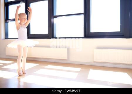 Petite fille formation pour être une ballerine debout dans un bras gracieux position relevée dans son tutu blanc Banque D'Images