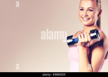 Young woman smiling, un haltère à l'épaule. Banque D'Images