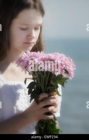 Une jeune fille tenant un bouquet de fleurs Banque D'Images