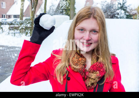 Young caucasian woman dressed in red holding snowball à jeter en hiver Banque D'Images