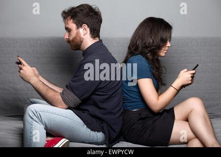 Jeune couple silencieux avec les smartphones sitting on a Couch