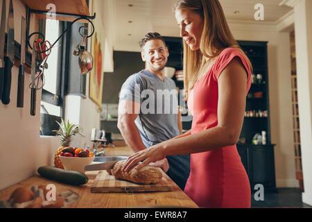 Tourné à l'intérieur du jeune homme et de la femme dans la cuisine le matin. L'accent sur le pain coupe femme, préparer Banque D'Images