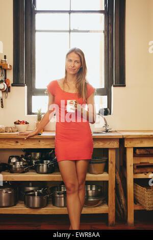 Portrait of attractive young woman in red dress debout dans la cuisine avec une tasse de café. Beau modèle féminin ayant des
