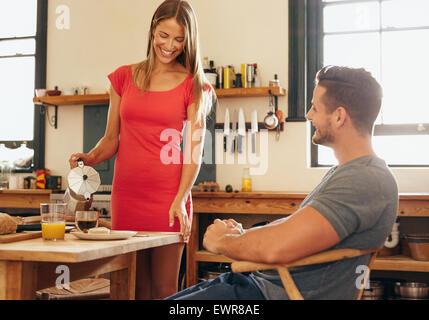 Tourné à l'intérieur du couple having breakfast in cuisine. Young woman pouring coffee dans une tasse avec l'homme Banque D'Images