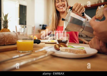 Piscine shot of woman pouring coffee dans une tasse. Woman smiling tout en servant le petit-déjeuner à l'homme dans Banque D'Images