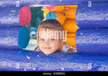 Fille de cinq ans jouant sur l'aire de jeux a l'air à partir d'une fenêtre en bois Banque D'Images