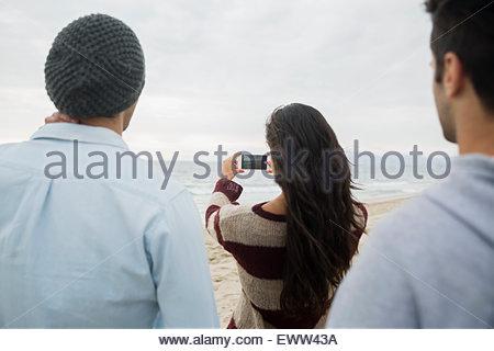Les amis de photographier avec l'océan téléphone appareil photo on beach Banque D'Images