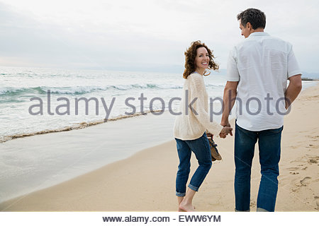 Young couple holding hands walking on beach Banque D'Images