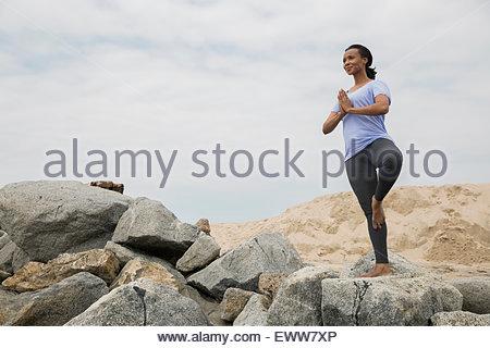 Woman in yoga posture de l'arbre sur les rochers plage Banque D'Images
