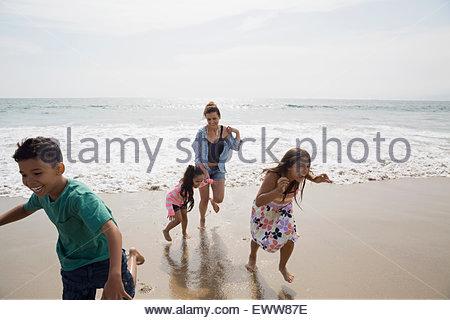 L'exécution de la famille d'ocean sur sunny beach Banque D'Images