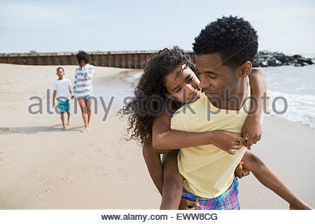 Père fille piggybacking on beach Banque D'Images