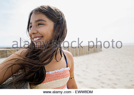 Portrait smiling girl sitting on sunny beach Banque D'Images