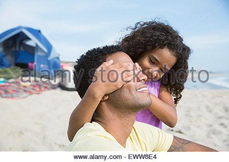Fille couvrant les yeux père on beach Banque D'Images