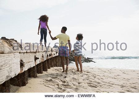 Marcher le long de la famille plage mur Banque D'Images
