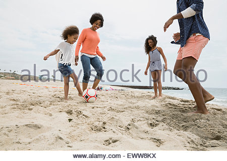 Family playing soccer on beach Banque D'Images