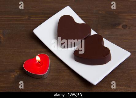 Bougie et chocolats en forme de coeur sur table en bois Banque D'Images