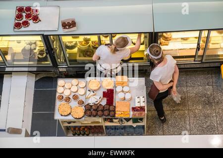 Les femmes de l'affichage de la préparation des gâteaux et des pâtisseries maison à vendre à shopping centre cafe. Banque D'Images