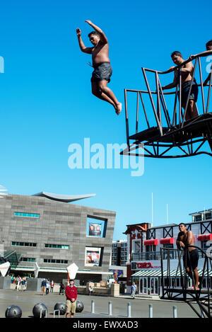 Les jeunes hommes de sauter d'une plate-forme à l'heure du déjeuner à côté de musée national Te Papa à Wellington, Banque D'Images