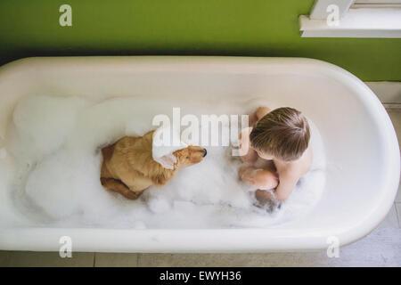 Vue en hauteur d'un garçon et de son chien assis dans une baignoire Banque D'Images
