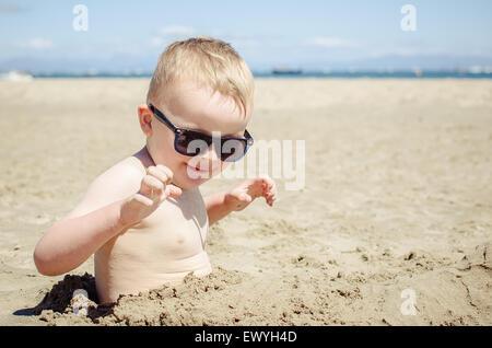 Garçon enterré dans le sable sur la plage Banque D'Images