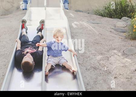 Deux garçons jouant sur une diapositive à l'aire de jeux Banque D'Images