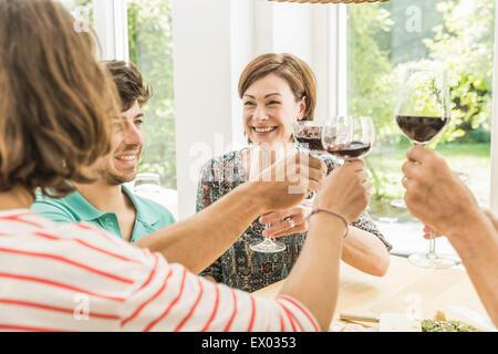 Cinq amis adultes faire un toast au dîner Banque D'Images