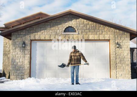 Homme de pelleter de la neige, Young's Point, Ontario, Canada Banque D'Images