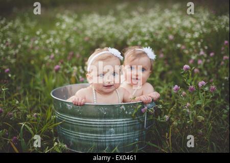 Portrait de deux sœurs jumelles bébé baignant dans un bain d'étain dans une prairie de fleurs sauvages Banque D'Images