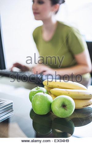 Pomme verte et les bananes, young woman using computer in background Banque D'Images