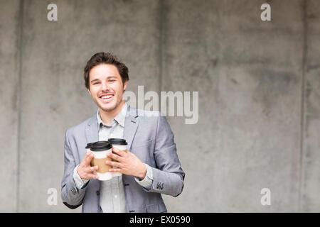 Businessman holding tasses à café jetables Banque D'Images