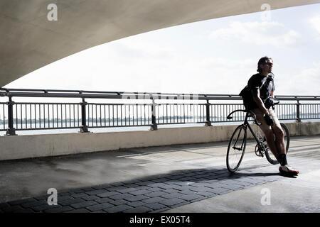 Bike messenger leaning on bike Banque D'Images