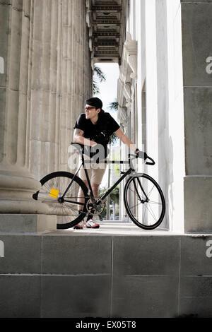 Bike messenger en tenant la colonne à côté de pause Banque D'Images