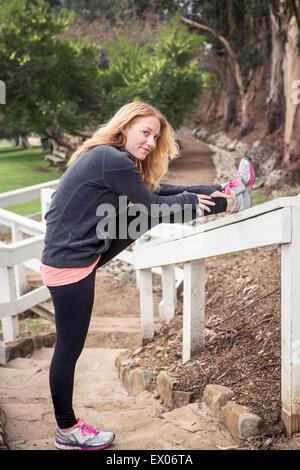 Young female runner se réchauffer sur l'escalier du parc Banque D'Images