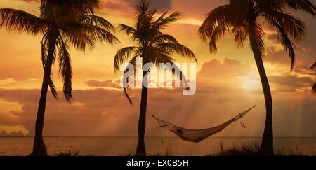 Jeune femme couchée sur un hamac au coucher du soleil sur Miami Beach, Floride, USA Banque D'Images