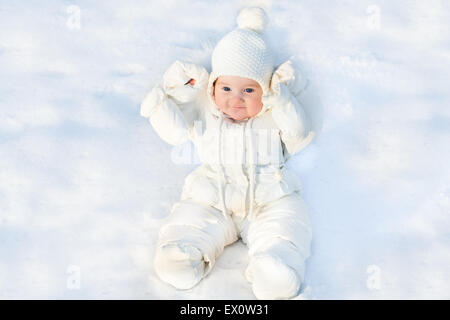 Drôle de petit bébé assis dans la neige fraîche portant une veste blanche et un chapeau en tricot chaud Banque D'Images