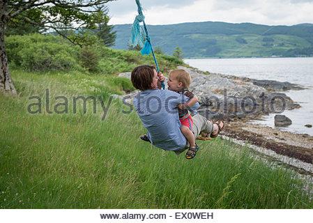 Une mère et son jeune fils sur une corde-swing à côté d'un loch écossais Banque D'Images