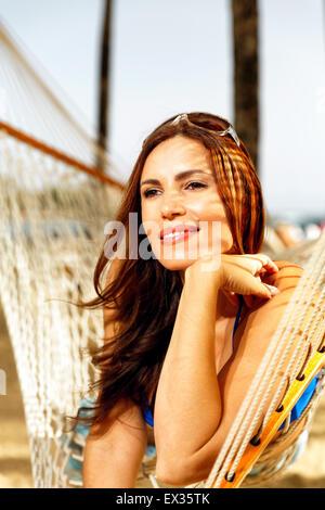 Low Angle View of a young woman Relaxing on a Beach dans un hamac avec tête posée sur une main, San Juan, Puerto Banque D'Images