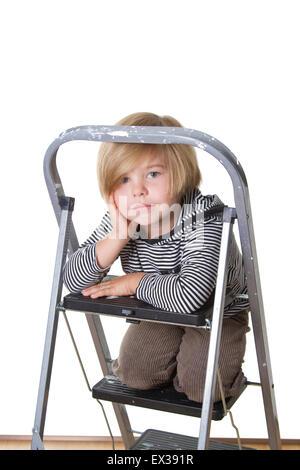 Jeune garçon portant chemise rayée et le capot, assis sur une échelle, souriant à la caméra. Banque D'Images