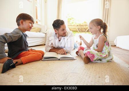 Famille avec livre assis sur étage avec petite fille parle à son père et son frère. Père avec son petit garçon et Banque D'Images