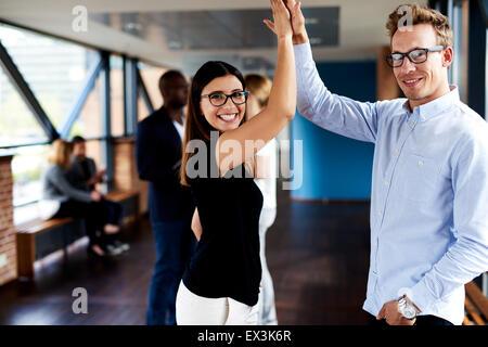 Les hommes et les collègues et on subit donc haut smiling at camera Banque D'Images