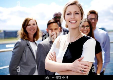 White female executive debout devant des collègues avec les bras croisés en souriant. Banque D'Images
