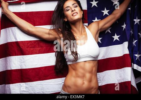 Sporty young woman holding American flag. Femme de remise en forme parfaite avec l'abs. Banque D'Images