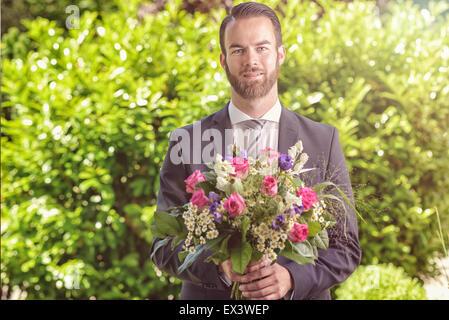 Beau jeune homme barbu en costume portant un bouquet de fleurs fraîches, peut-être un prétendant ou beau appeler Banque D'Images