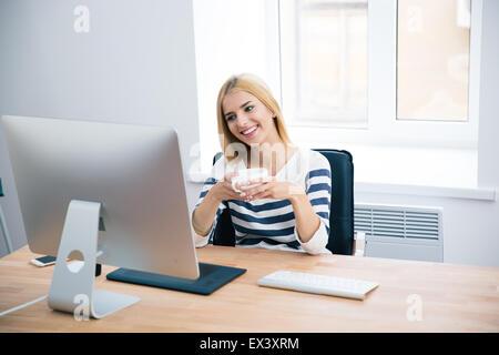 Happy female designer assis à la table avec les ordinateurs de bureau et de boire du café in office Banque D'Images