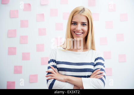 Smiling young casual Girl standing with arms folded in office avec des autocollants sur l'arrière-plan Banque D'Images
