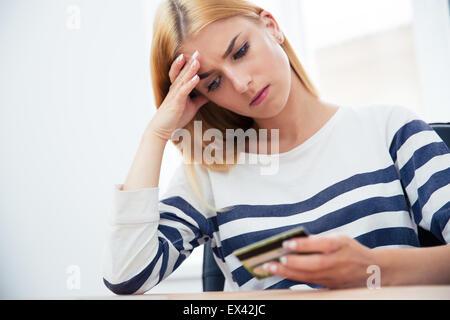 Malheureux casual woman holding bank card Banque D'Images