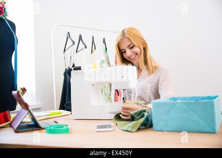 Happy female adapter l'utilisation de machine à coudre dans une laverie Banque D'Images
